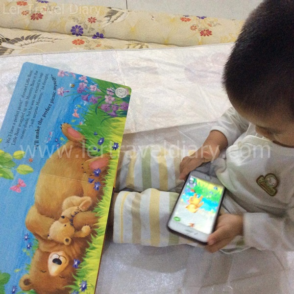 Chen is listening to the story through Magic Hippo app and book.